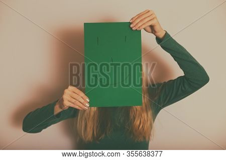 Woman With Happy Face On Paper Standing In Front Of Wall.
