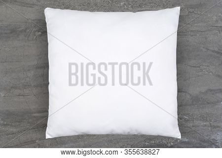 A White Throw Pillow Elegantly Reclines Atop A Luxurious Gray Marble Background. Plenty Of Copy Spac