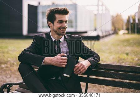 Elegant Businessman Enjoys Drinking Coffee While Sitting Outdoor