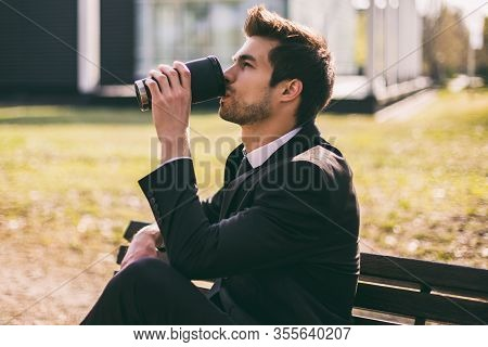 Elegant Businessman Enjoys Drinking Coffee While Sitting Outdoor.