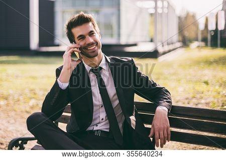 Elegant Businessman Using Phone While Sitting Outdoor