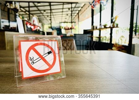 No Smoking Sign On A Wooden Table Of Coffee Shop In Hotel Room. Concept Photo Of Banning Smoking In