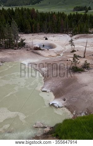 Sulphur Caldron At Yellowstone National Park With Bubbling, Sulphur Smelling Water In A Barren Lands