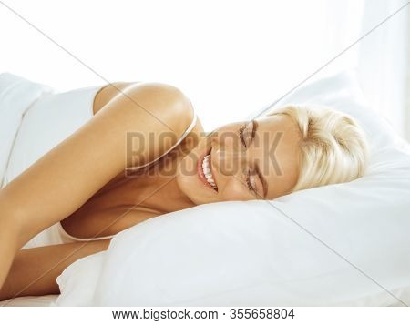 Beautiful Young Woman Sleeping While Lying In Bed Comfortably And Blissfully. Good Morning Concept