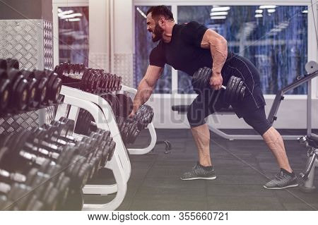 Strong Young Man With Beard Wearing Black Jersey And Shorts Lifting Heavy Weight Barbell In Sport Gy
