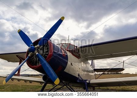 White Biplane Standing On Airports With Cloud Sky