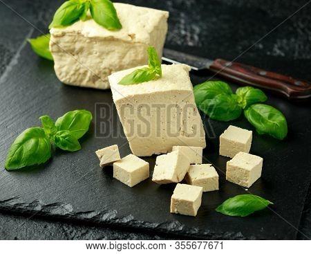 Organic Soy Tofu With Basil On Dark Rustic Stone Board