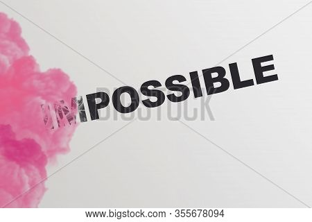 Word Impossible Turning Into Possible With Pink Smoke. Startup Business Motivation Concept