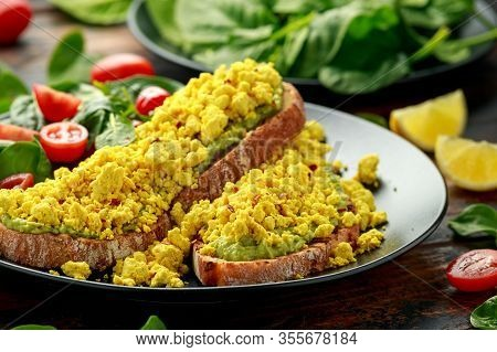 Scrambled Tofu Crispy Toast With Guacamole And Spinach, Tomato Salad. Vegan Vegetarian, Plant Based