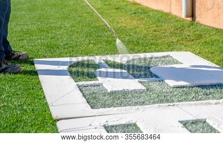 Draw Letters On The Grass In White Over A Template. The Name Of The Football Field On The Grass