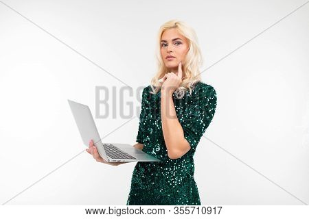 Stylish Lady In A Shiny Dress Pensively Thinking About A Proposal On A Laptop Screen On A White Back