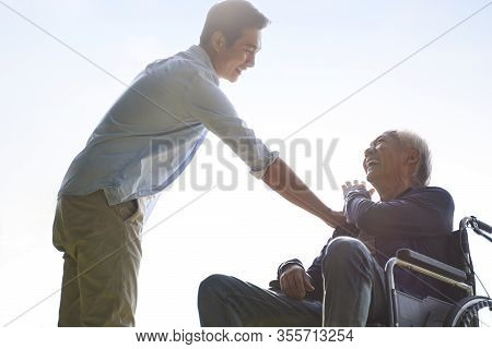 Young Asian Adult Son Giving Dad A Pat On The Shoulder, Happy And Smiling