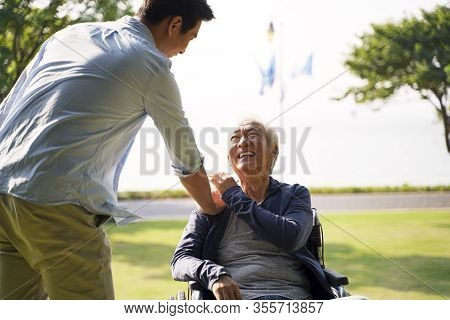 Young Asian Adult Son Visiting Father In Nursing Home Giving Dad A Pat On The Shoulder
