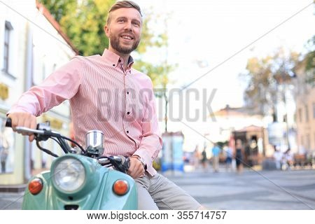 Handsome Man Posing On A Scooter In A Vacation Context. Street Fashion And Style.