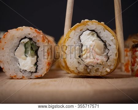 Close Up One Peace Of Sushi Roll Held With Wooden Chopsticks. Japanese Cuisine. Sushi Roll With Tama
