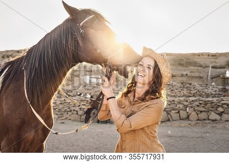 Young Farmer Having Fun With Horses Inside Stable - Happy Girl Playing With Animals In Corral Ranch