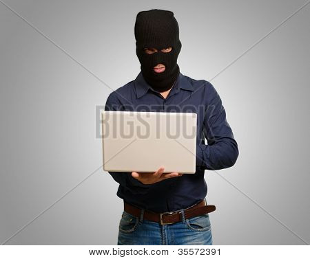 young male thief holding a laptop isolated on a grey background