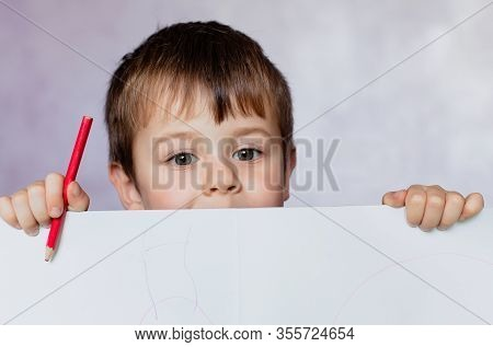 Funny Child Boy Looks For A Drawing Album. Little Boy Is Holding Color Pencils.