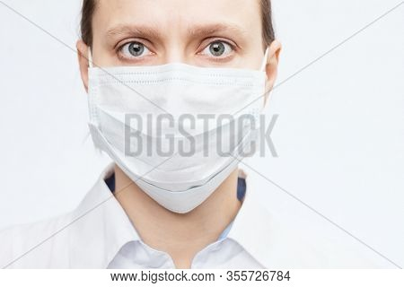 Close-up portrait of confident young female doctor wearing protective surgical mask - epidemic virus outbreak concept