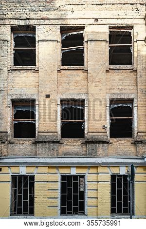 Destroyed Dirty Facade. Broken Windows. Facade Of Old Collapsing Town House With Broken Windows And