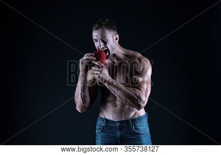 Eating Heart Healthy Diet. Bodybuilder Pretend Eating Red Heart. Cardiac Diet. Bodybuilding Diet. Di