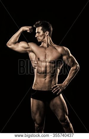 Athlete Flex Arm With Biceps, Triceps. Man Show Muscular Body. Bodybuilder With Bare Torso, Six Pack