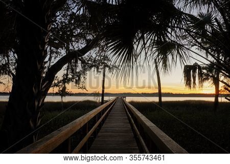 Sunset On Spring Island, South Carolina; View Of A Long Dock Leading Out Into The Callawassie River