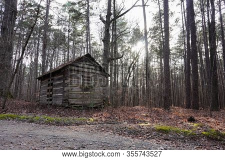 The Sun Peeks Through The Trees Of The Woods With An Old Log Cabin In Winter; Landscape
