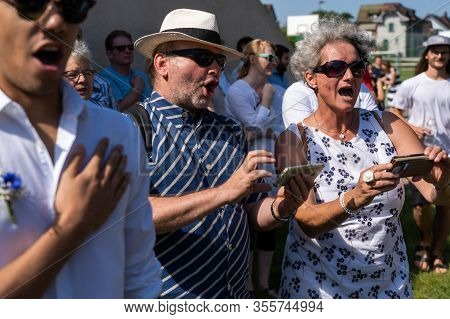 People Holding Their Mobile Phone With Lyrics While Singing The Favorite Hymn On The 4th Of July At