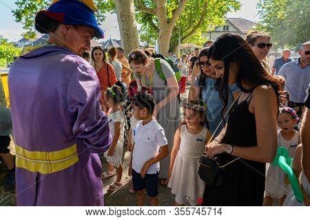 Children Standing In Line For Choosing A Balloon From A Friendly Balloon Artist At A Summer Festival
