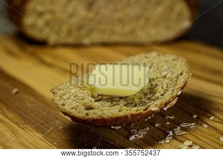 Slice Of Multi Grain Bread With A Pat Of Butter On A Cutting Board