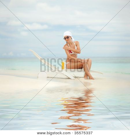 Young woman with sun-protection cream on the beach