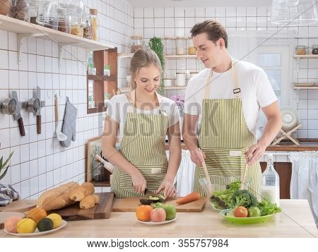 Happy Caucasian Couple Family Cooking In Modern Kitchen At Home With Love. Married Romantic Man And