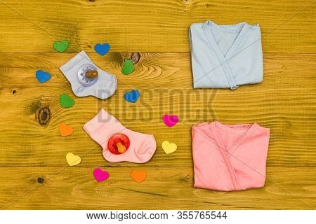 Baby Supplies For Boy And Girl And Heart Shapes On Wooden Table.baby Announcement Concept.