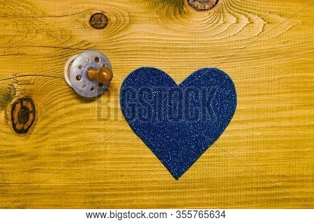 Blue Pacifier For Baby Boy With Heart Shape On Wooden Table.baby Announcement Concept