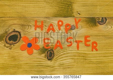 Happy Easter Message With Flower On Wooden Table.