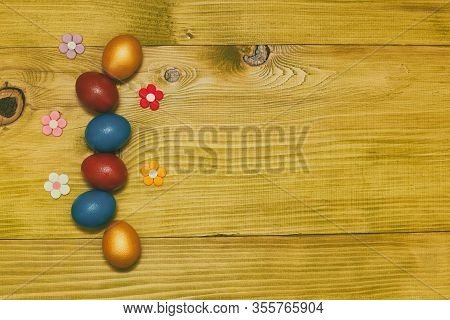 Painted Easter Eggs With Petals On Wooden Table.