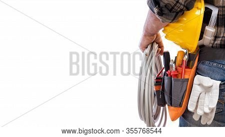View From Behind, Electrician Holds The Roll Of Electric Cable In His Hand, Helmet With Protective G
