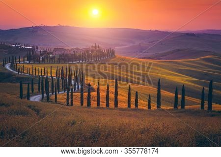 Magical Tuscany Landscape With Grain Fields, Cypress Trees And Houses On The Hills At Sunset. Autumn