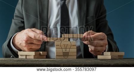 Business Vision And Strategy Conceptual Image - Businessman Assembling A Light Bulb Drawn On Wooden