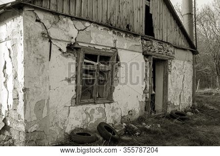 Old Abandoned Building With Ruined Windows And Walls. Huge Large Cracks In Old Brick Wall. Abandoned