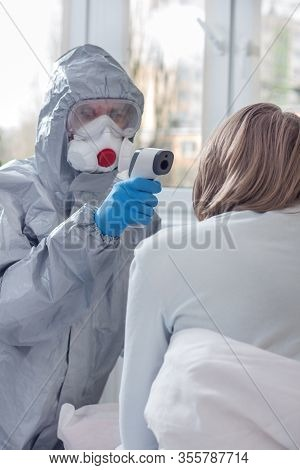 Checking The Temperature With A Laser Thermometer By A Person In A Protective Suit, Protective Mask