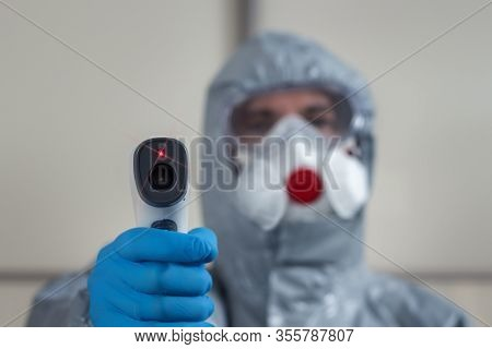 In The Foreground A Hand Wearing A Disposable Glove Holds A Laser Thermometer And Measures The Tempe