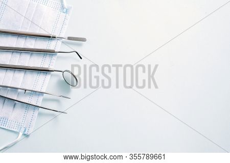 Dentist Instruments: Mirror And Dental Probe Lying Left On Medical Mask On Light Blue Background. Pa