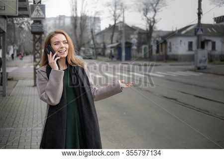 Beautiful Woman Talking On The Phone At The Tram Stop. Urban Transport Waiting Concept.