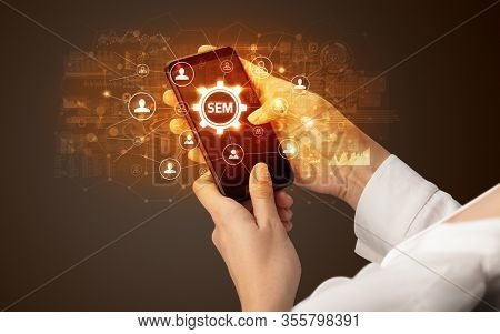 Female hand holding smartphone with SEM abbreviation, modern technology concept