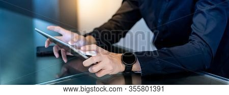 Businessman Hand Using Digital Tablet In Office Meeting Room. Male Entrepreneur Reading News On Soci