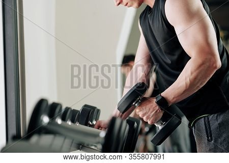 Sportsman Picking Dumbbell To Exercise With And Taking Heavy One Out Of Set Of Black Weights