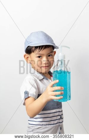 Asian Boy Holding Bottle Of Alcohol Gel For Cleaning Baby Hands To Prevent Against Infection Of Covi
