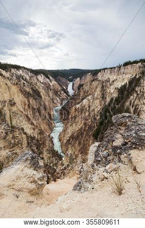 The Tall And Powerful Lower Falls Of The Yellowstone River As It Falls Into The Steep Canyon As Seen
